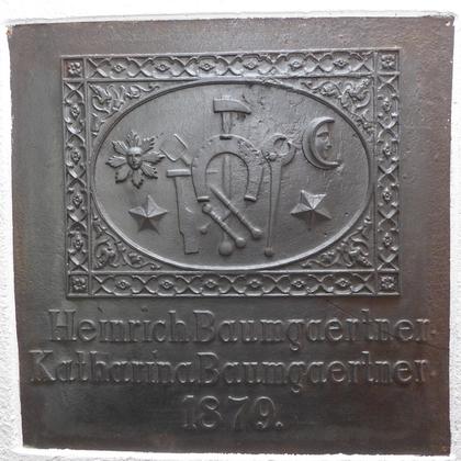 Ofenplatte der Huf- und Wagenschmiede von Johann Heinrich und Maria Katharina Baumgärtner, 1879